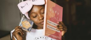 Woman wearing a headband and holding face masks from a subscription kit